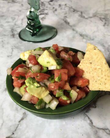 pico de gallo with avocado dip in a green bowl
