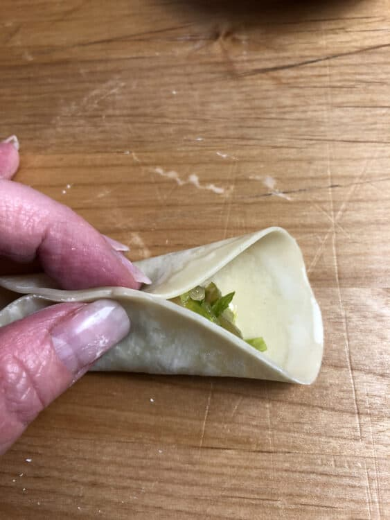 Begin pleating the Chinese dumpling