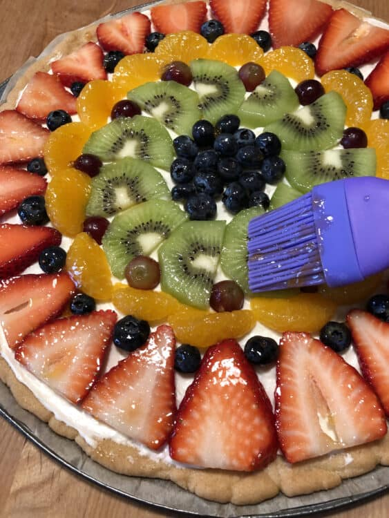 Brushing fruit pizza with jelly