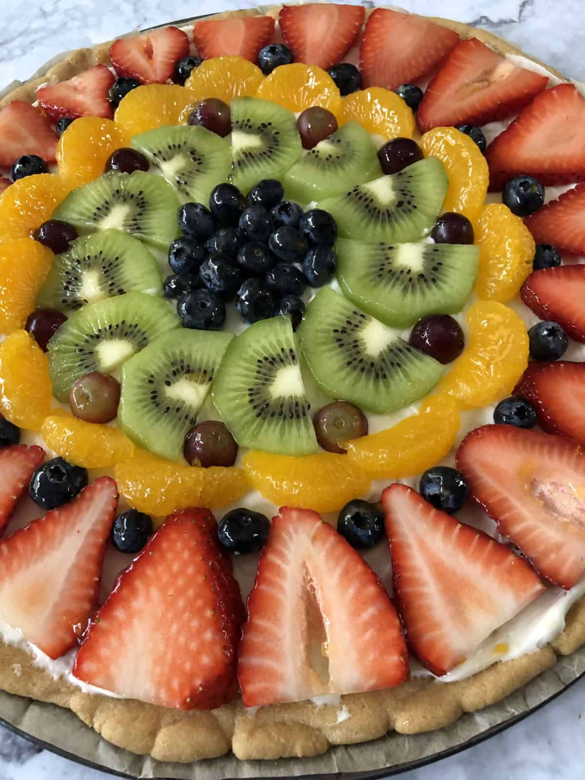 Fruit pizza close up with berries, kiwi and orange slices