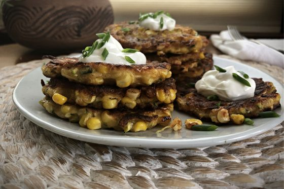 Zucchini and corn fritter stacked on a plate