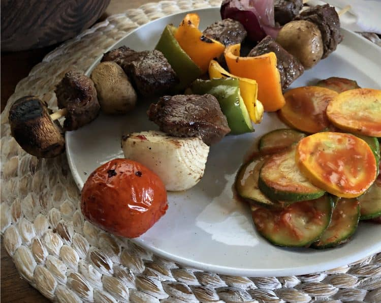 beef kabobs on plate with zucchini