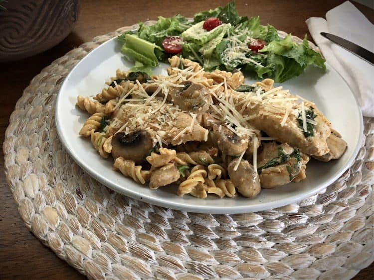 sun dried tomato (red) pesto chicken on a plate with a salad