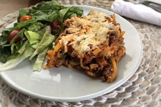 butternut squash spaghetti bake on a white plate with salad