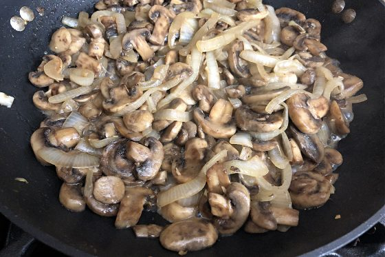 Sauteed mushrooms and onions in a pan