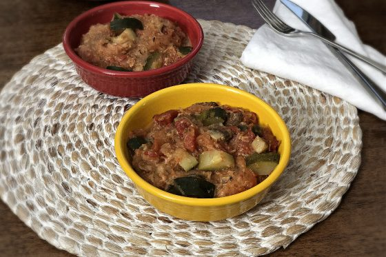 vegetarian spaghetti squash casserole in two bowls, red and yellow