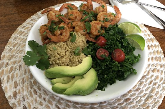 chili lime shrimp in a bowl with quinoa kale and avocado
