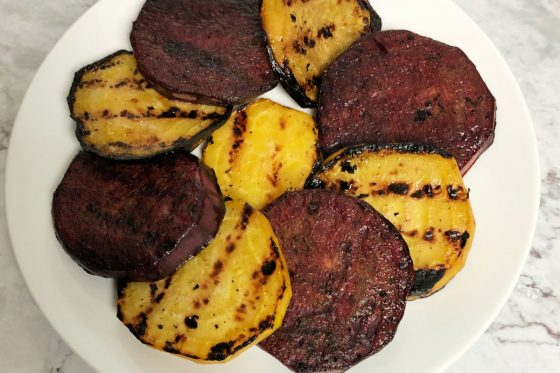 grilled red and golden beets on a white plate