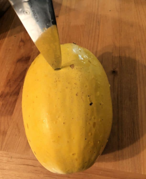 knife poking holes in the skin of the squash