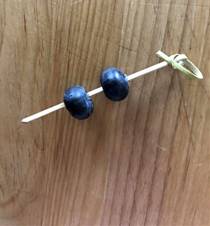 2 blueberries speared by a bamboo pick