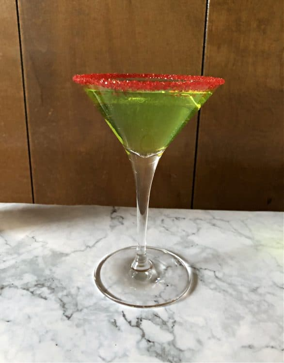 martini galss with red sugar rim and green drink