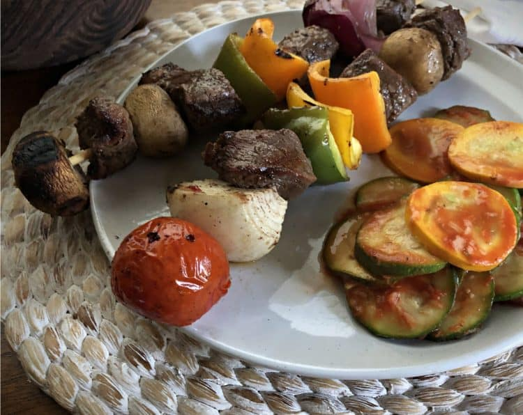 Beef kabobs on a plate with zucchini