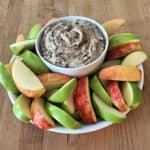 bowl of heath bar apple dip surrounded by slices of red and green apple