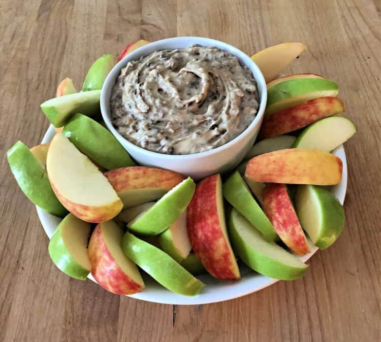 bowl of heath bar dip surrounded by slices of red and green apple
