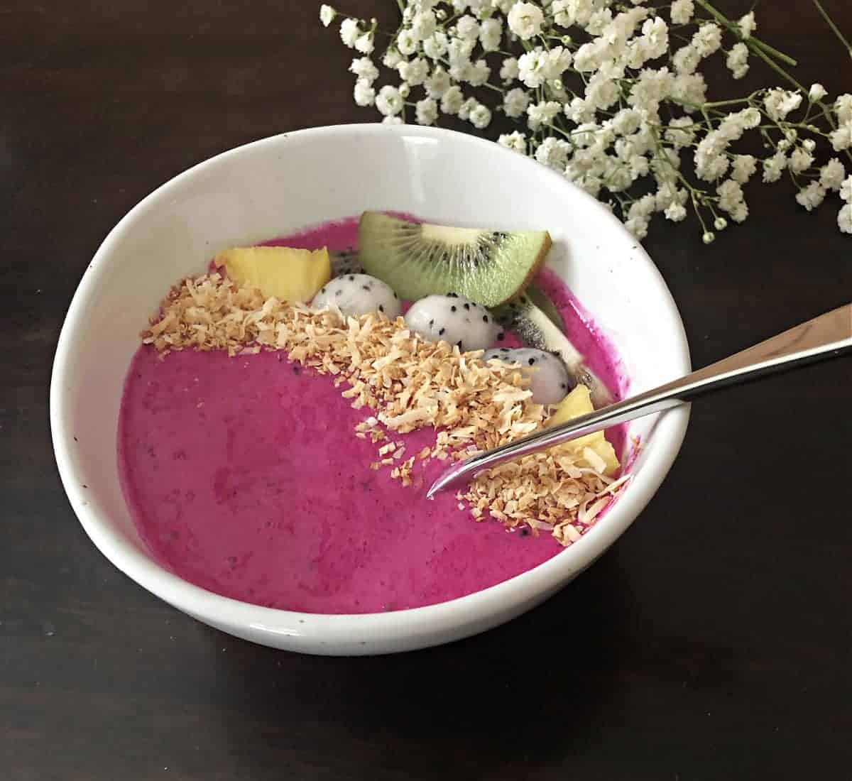 dragon fruit smoothie bowl garnished with toasted coconut and kiwi