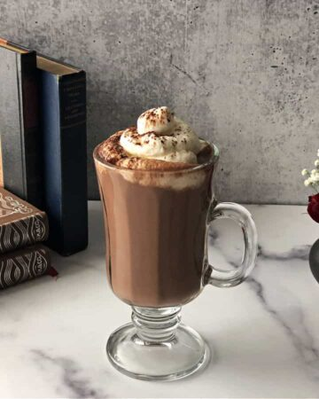 keto hot cocoa with whipped cream next to some books