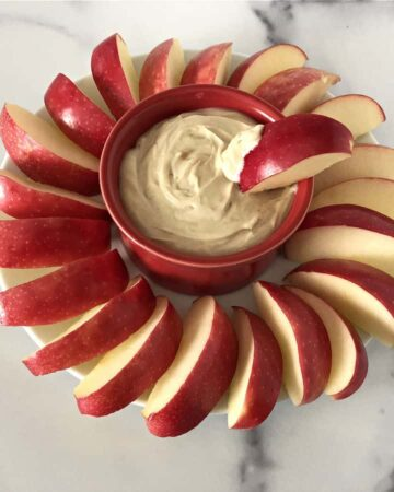 greek yogurt with peanut butter dip surrounded by apple slices
