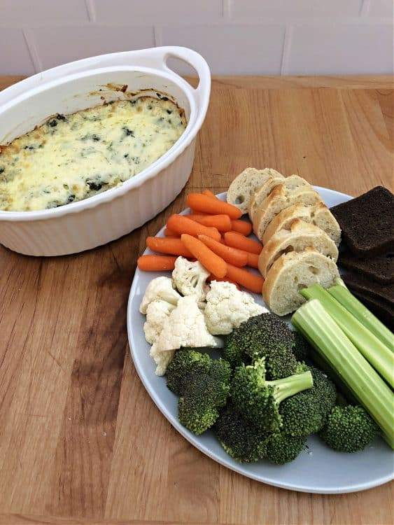 spinach artichoke dip next to a plate of breads and veggies