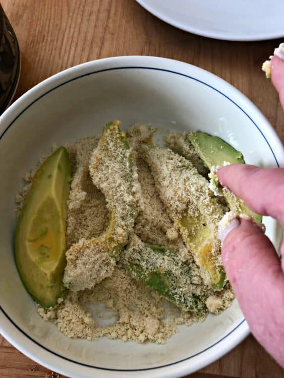 hand placing avocado slices in the bowl of meal