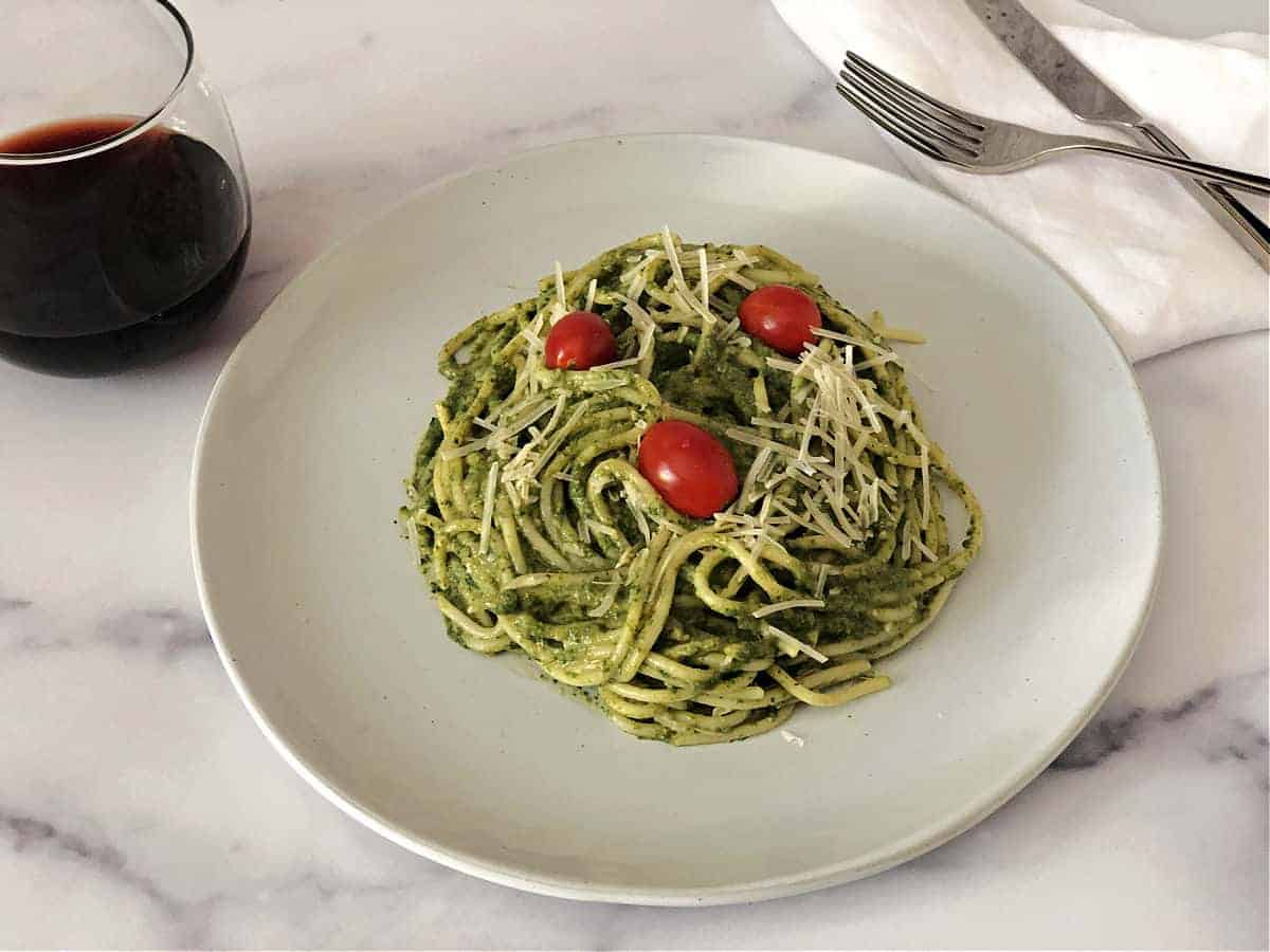 green pasta sauce on spaghetti noodles, on a white plate