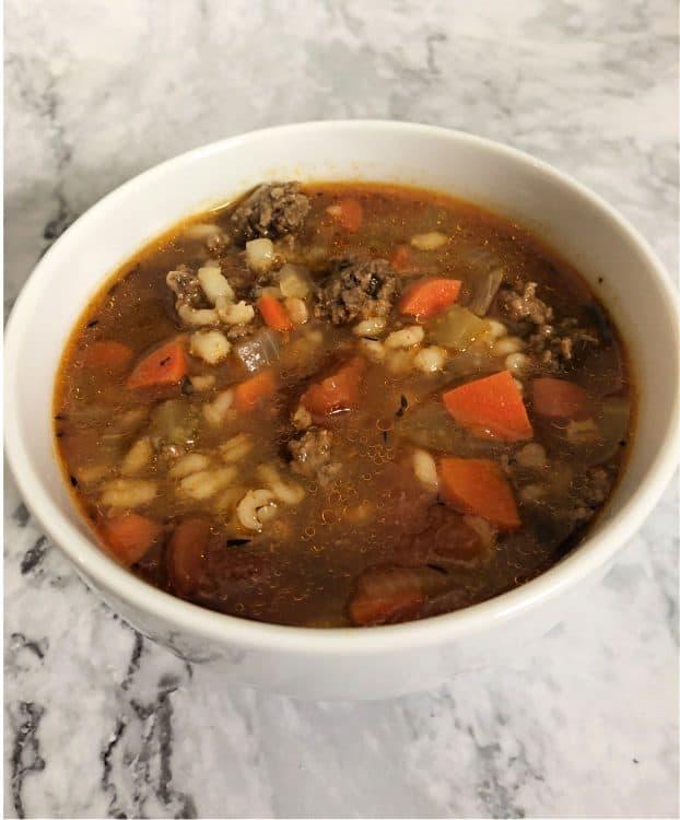 Hamburger barley soup in a white bowl