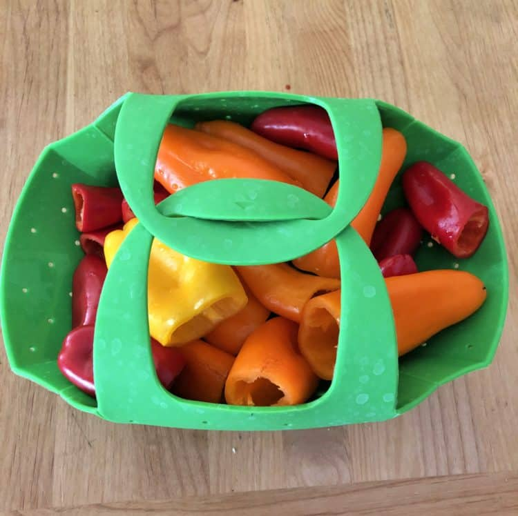 mini peppers in agreen steamer basket, closed and ready to cook