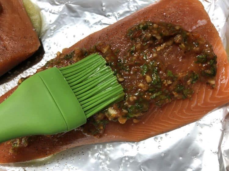 spreading sauce on raw salmon