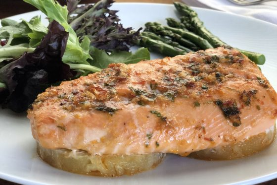 baked pineapple salmon on a white plate with salad and asparagus