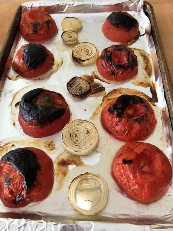 roasted tomatoes and onions on a baking sheet