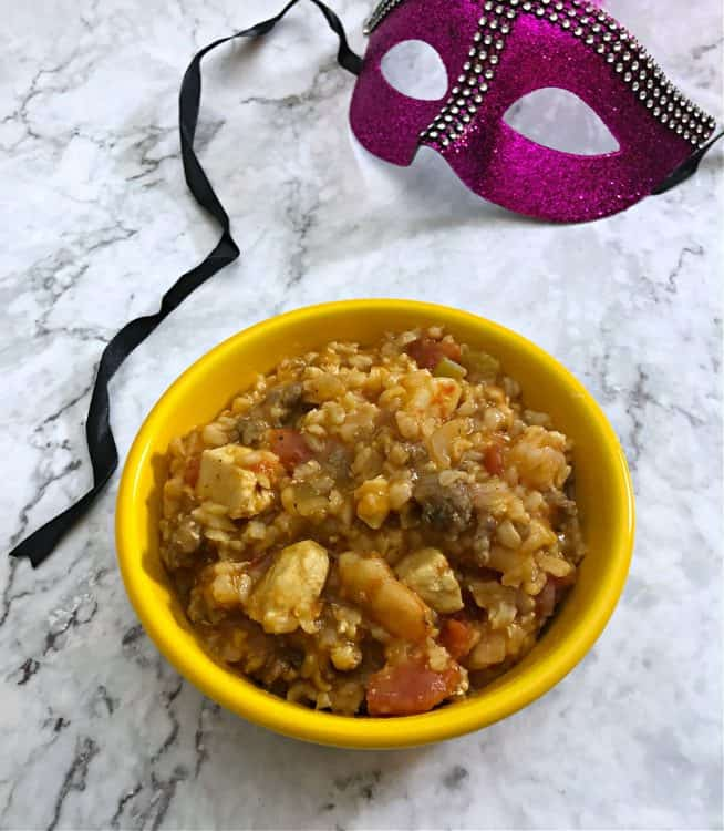 Jambalaya in a yellow bowl with a mardi gras mask nearby