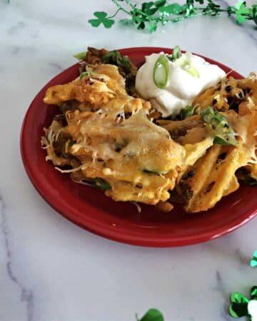 Irish Nacho style waffle fries on a red plate