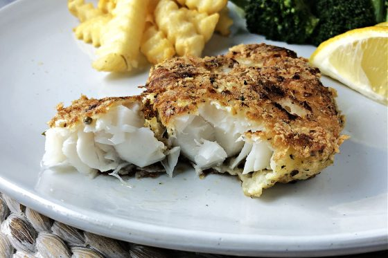 Potato crusted cod on a white plate