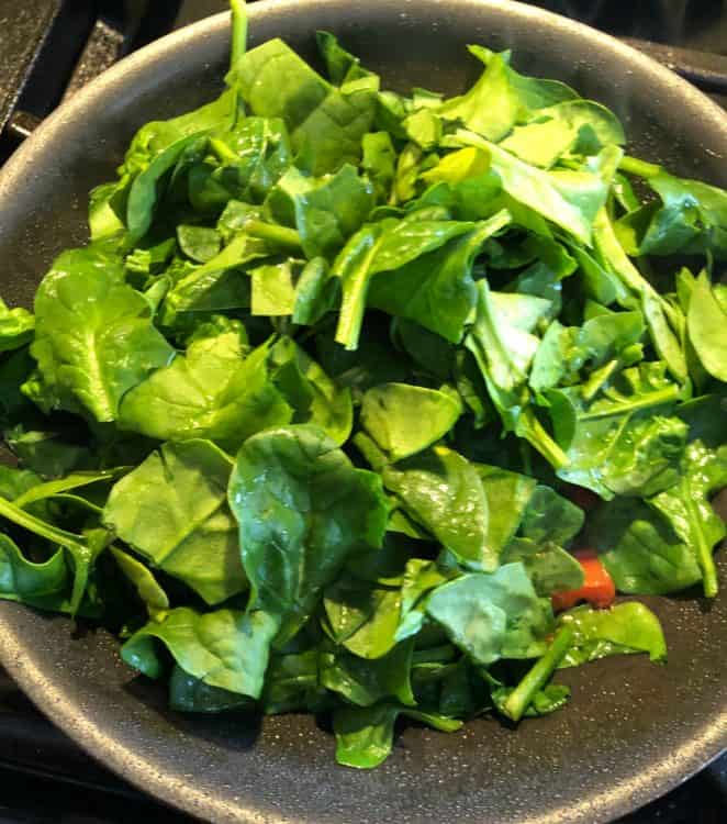 fresh spinach added to skillet