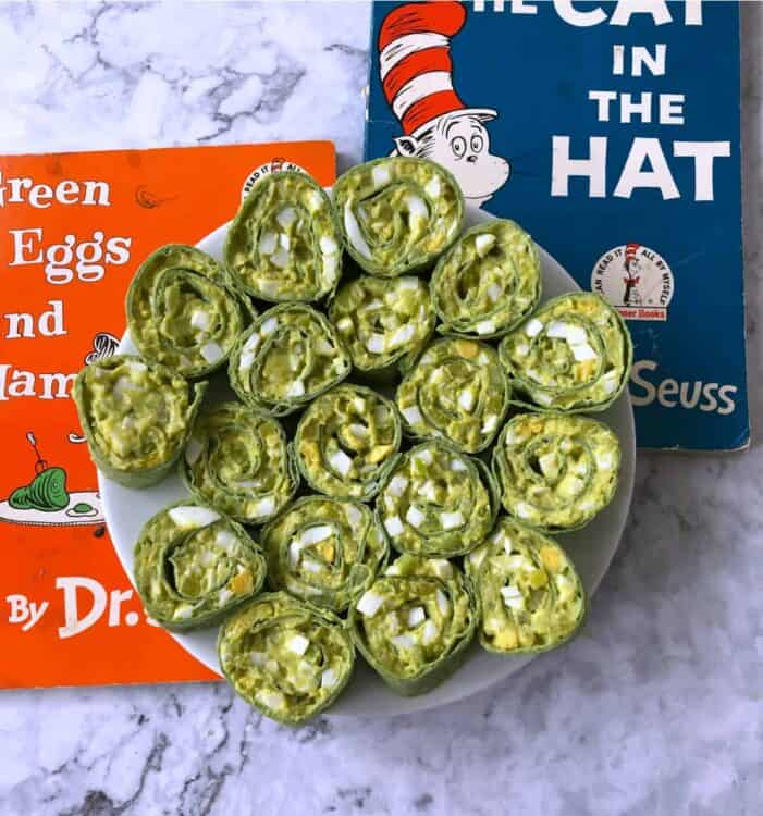 Egg salad pinwheels on a white plate with Dr Seuss books behind