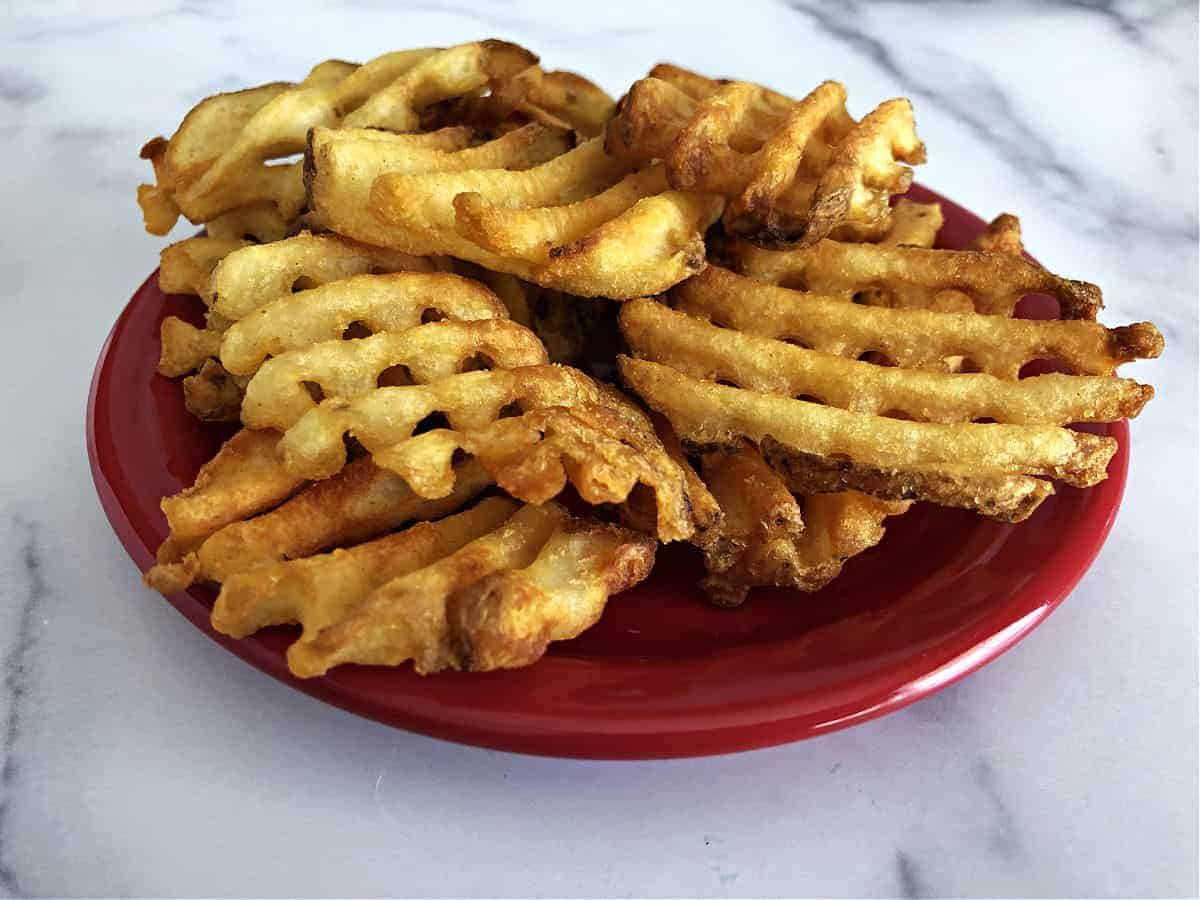 Waffle fries on a small red plate