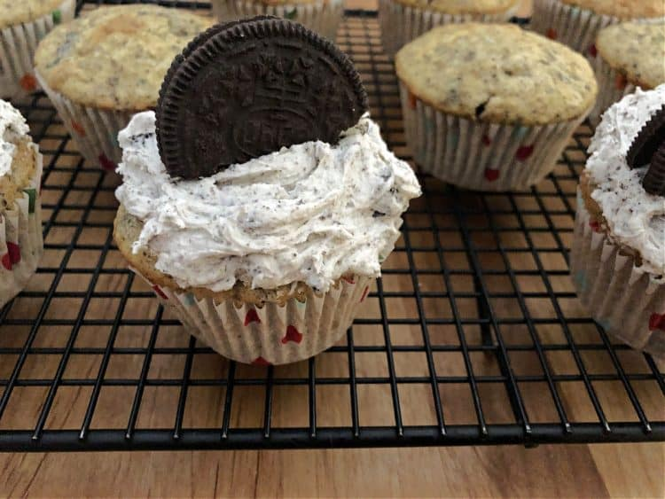 Decorated cupcake on a rack with undecorated ones