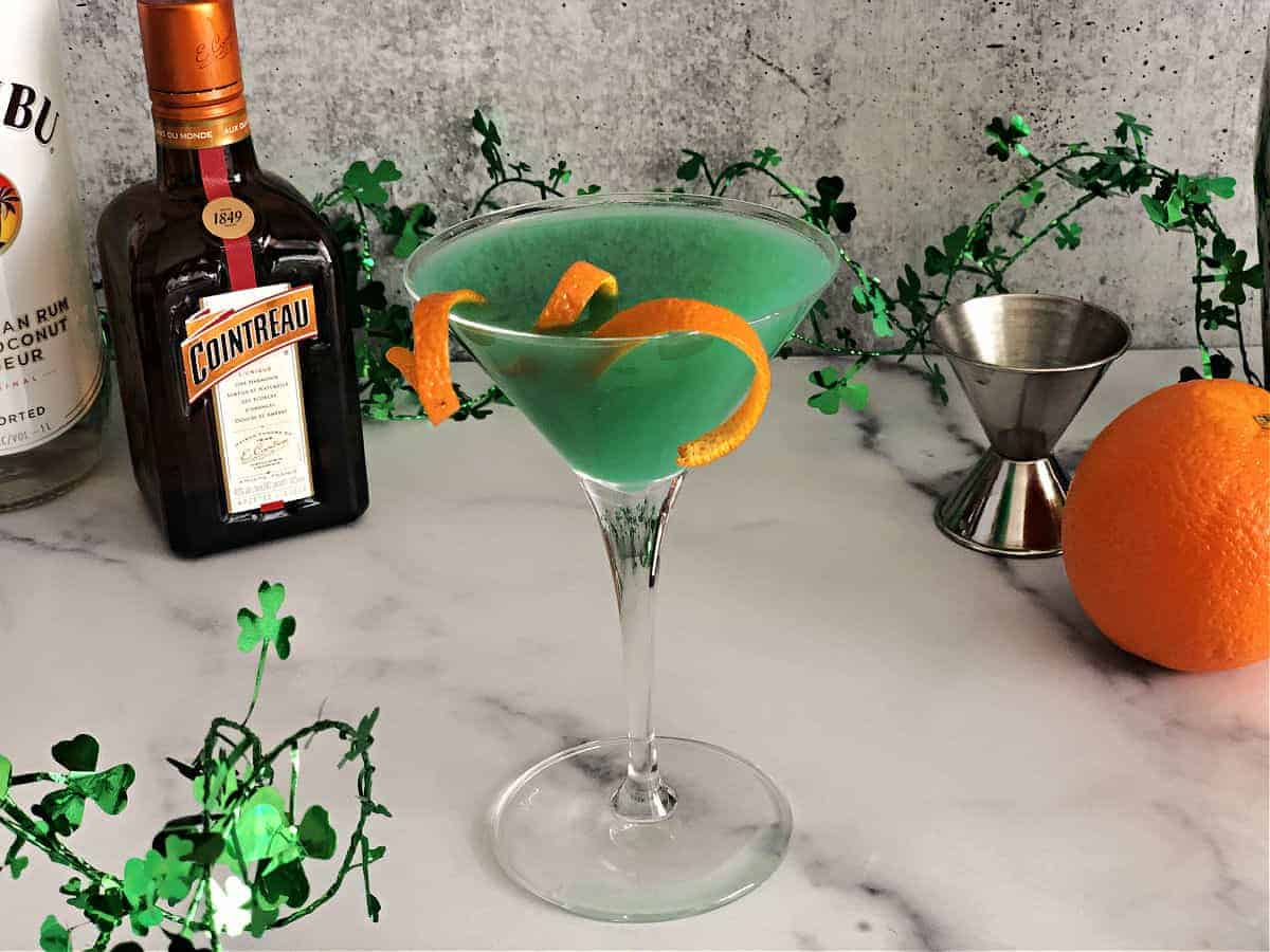 Shamrock martini surrounded by ingredients and clover garland
