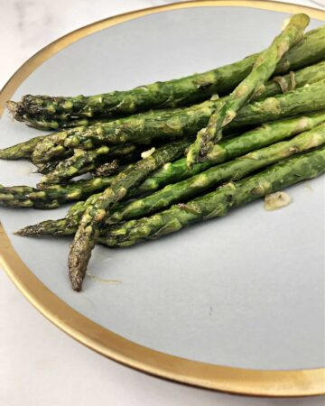 pan fried asparagus on a gold rimmed plate