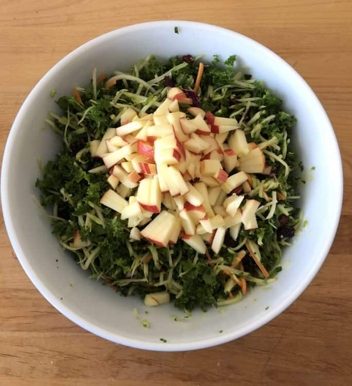chopped apples added to the salad in a bowl