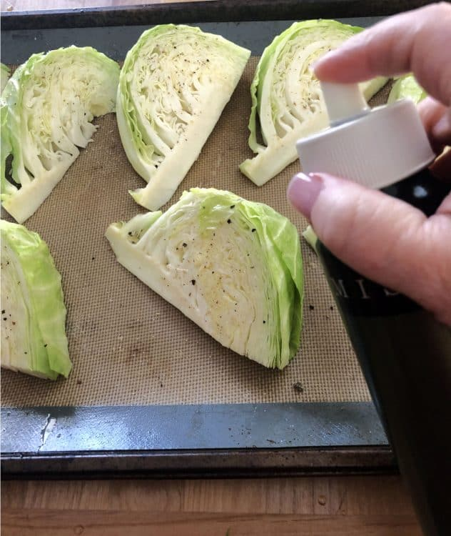 mister spraying oil on the wedges of cabbage