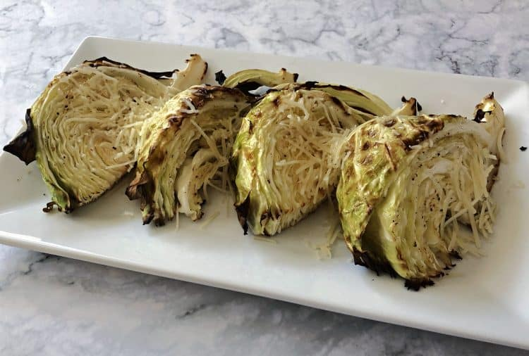 Roasted cabbage wedges on a white platter