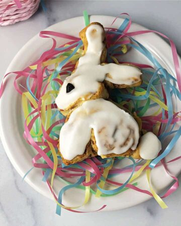 Easter bunny cinnamon roll on a white plate with pastel pretend grass