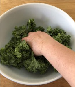 squeezing kale leaves in a bowl