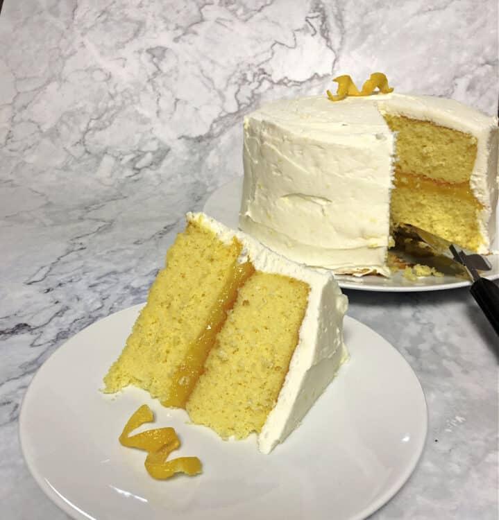 slice of lemon cake with whole cake behind