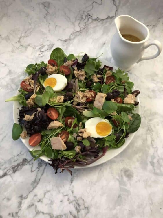 Nicoise salad with small pitcher of dressing nearby