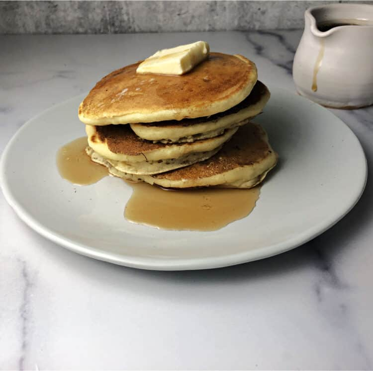 almond milk pancakes with butter and syrup on a white plate ready to eat