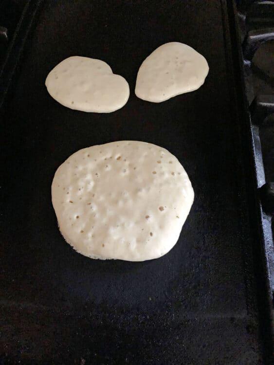 pancake batter cooking on a griddle