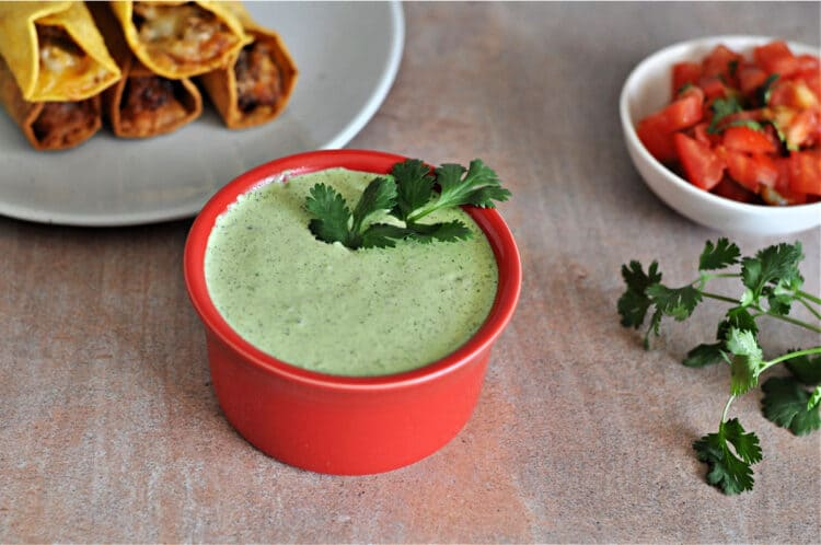 Cilantro Lime sauce in a small red bowl with taquitos behind it