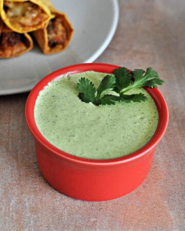 cilantro lime sauce in a small red bowl