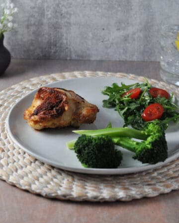 air fryer chicken thigh on a plate with salad and broccoli